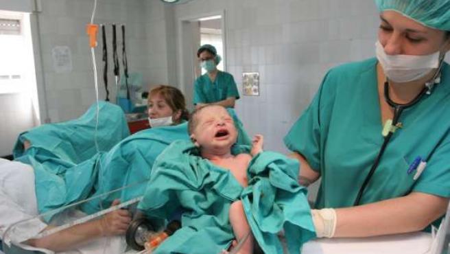 Una enfermera sostiene a un recién nacido.