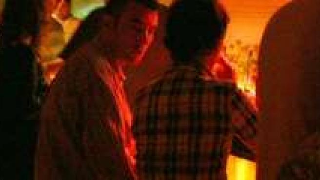Un grupo de personas toma una copa en un pub.