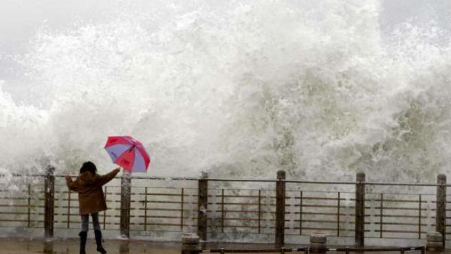 Un mujer se ve sorprendida por una ola mientras camina por el Paseo Nuevo de San Sebastián. (EFE/JAVIER ETXEZARRETA)