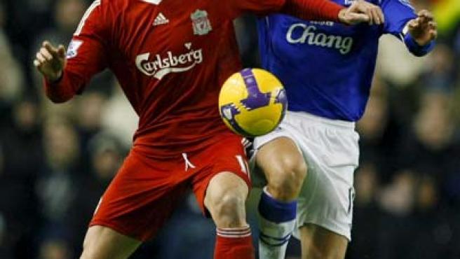 Riera y Phill Neville pugnan por un balón.