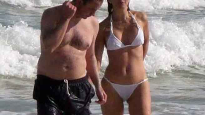Ingrid Betancourt pasea con un amigo por una playa de Miami.
