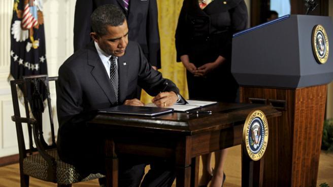 El presidente de EE UU firma un documento en la Casa Blanca.