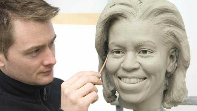 Uno de los artistas del museo de cera de Washington retoca la cabeza de la figura de Michelle Obama (EFE)
