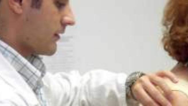 Un médico atiende en su consulta a una paciente.