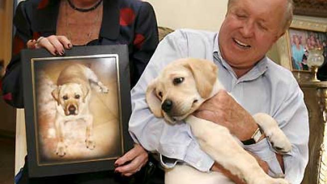 Edgar y Nina Otto posan con Lancelot y con una foto de su anterior perro. (Gary I Rothstein / EFE).