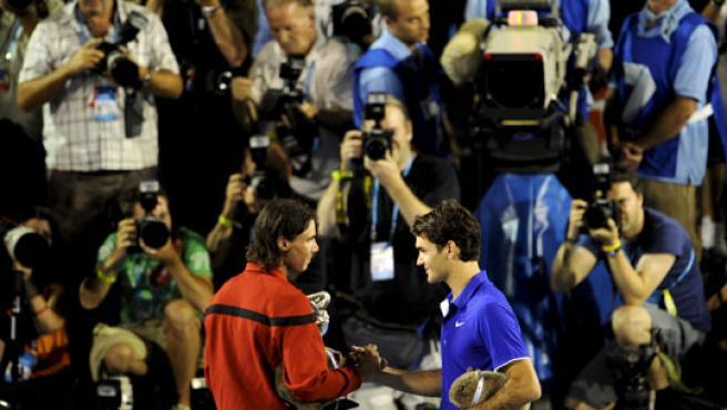 El español Rafael Nadal (i) y el suizo Roger Federer (d) posan tras la final masculina del Abierto de Australia. (EFE)