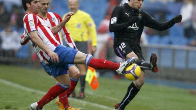 El centrocampista del Atlético Raúl García (i) y el también centrocampista Pedro León, del Valladolid (d), persiguen el balón. (EFE)