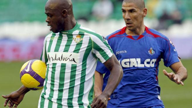 El centrocampista camerunés del Real Betis Achille Emana (i) y el defensa argentino del Getafe Daniel Alberto 'Cata' Díaz pugnan por un balón.