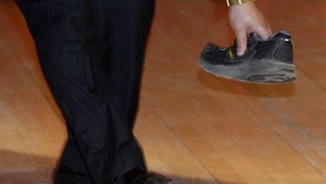 Un guardia de seguridad recoge el zapato que un manifestante arrojó al primer ministro chino (REUTERS).