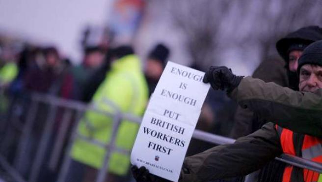 """Un trabajador inglés muestra un cartel que dice """"Es suficiente. Poned primero a los trabajadores británicos""""."""