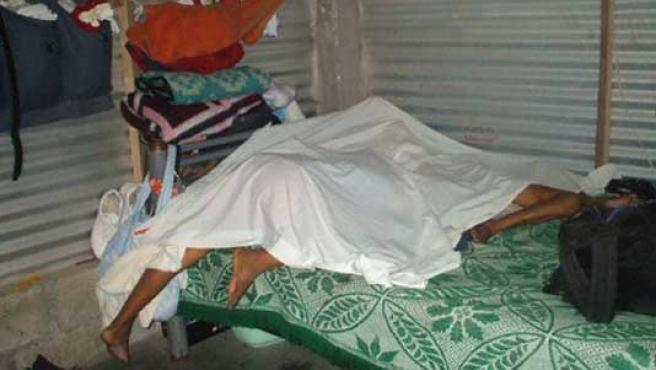 Varios cuerpos yacen en una humilde vivienda el 14 de febrero de 2009.