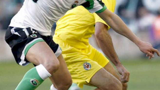 El defensa del Racing de Santander Juan Valera (i) conduce el balón ante el centrocampista francés del Villarreal Robert Pires. (EFE)