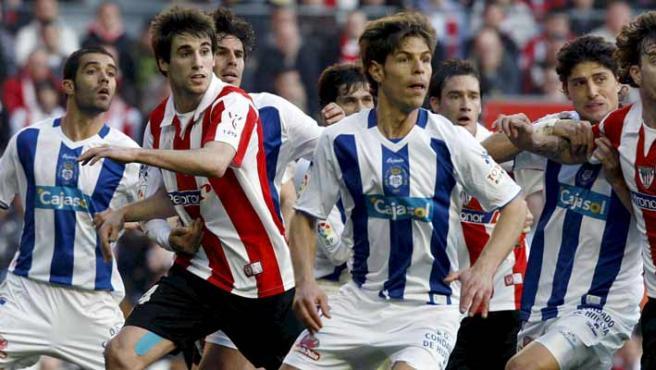 Jugadores del Athletic de Bilbao y del Recreativo de Huelva siguen la trayectoria del balón durante el partido. (EFE)