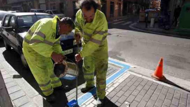 Dos trabajadores pintan la línea azul en la zona de la Circular.