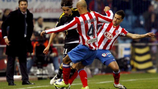 El defensa del Getafe, David Cortés (i), intenta marcharse del defensa del Atlético de Madrid, Mariano Pernía (c). (EFE)