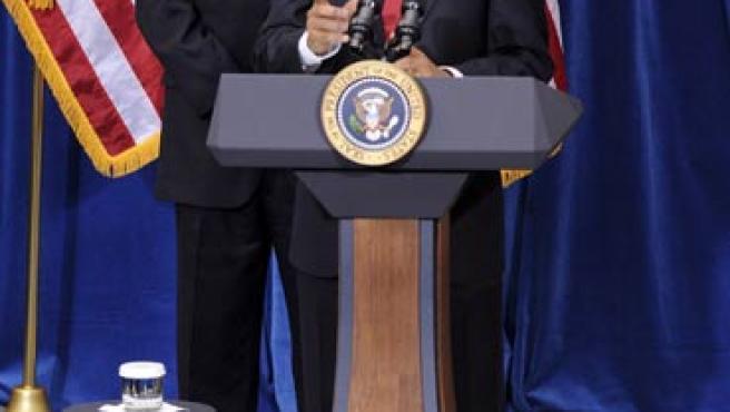 El presidente de EE UU, Barack Obama, respaldado por el vicepresidente, Joseph Biden, tras la firma de la ley (R. GIASE / EFE)
