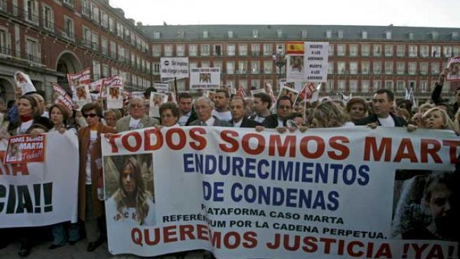 El abuelo, el padre y otros familiares de Marta del Castillp sostienen una pancarta en la Plaza Mayor de Madrid, durante la manifestación. (EFE)