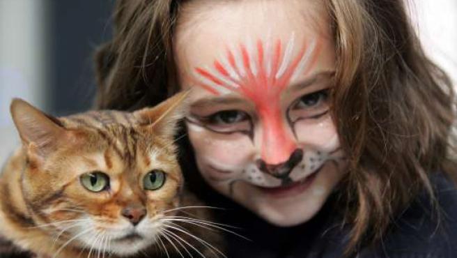 Una niña disfrazada posa junto a su gato.
