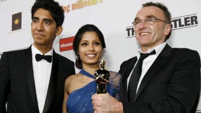 El director Danny Boyle sostienen el Oscar escoltado por Dev Patel y Freida Pinto.