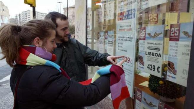 Una pareja mira las ofertas de una agencia de viaje.