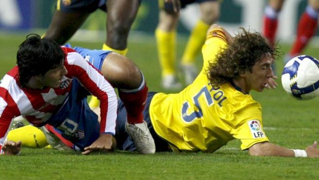"""El defensa del FC Barcelona Carles Puyol (d), pelea un balón con el delantero argentino del Atlético de Madrid, Sergio """"Kun"""" Agüero. (EFE)"""