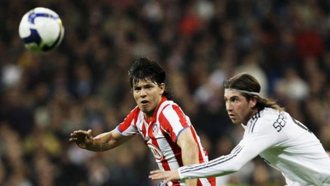 El 'Kun' Agüero, delantero del Atlético de Madrid, lucha por el balón con Sergio Ramos, defensa del Real Madrid.
