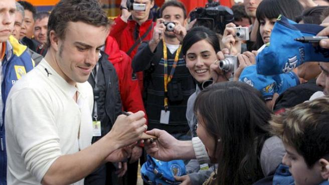 El piloto español de Renault Fernando Alonso (i) firma autógrafos a sus seguidores en el Circuito de Cataluña. Archivo.