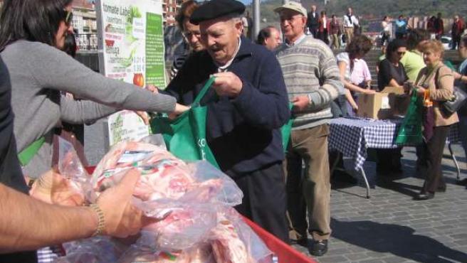 Un hombre recoge los productos que los agricultores y ganaderos vendieron en el Arriaga.