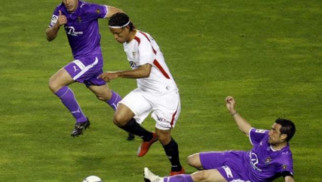 Luis Fabiano (centro) regatea a Luis Prieto y aguanta la presión de Iñaki Bea, del Valladolid.