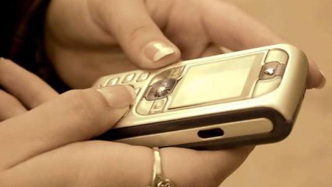 Una joven usando un teléfono móvil.