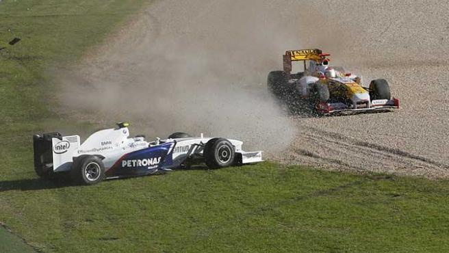 El BMW-Sauber de Nick Heidfeld (izq.) y el Renault de Fernando Alonso (dcha) se salen de la pista en la primera curva del GP de Australia.