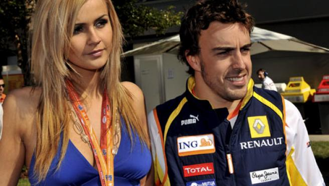 Fernando Alonso, de Renault, posa con una modelo en Melbourne (Australia).