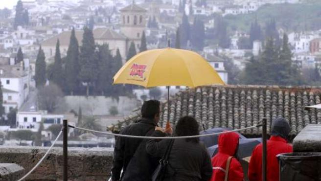 Turistas visitando Granada esta Semana Santa, protegiéndose del frío y la lluvia.