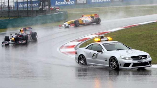 Sebastian Vettel (i), de Red Bull, circula detrás del coche de seguridad al comienzo del Gran Premio de China