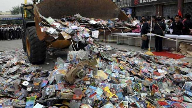 Un excavadora aplasta cientos de CDs pirata en China.