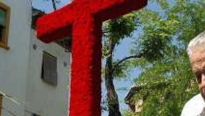 Un vecino del Albaicín, en Granada, ultima los detalles de la cruz.