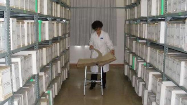 Una archivera examina un libro de bautismo.