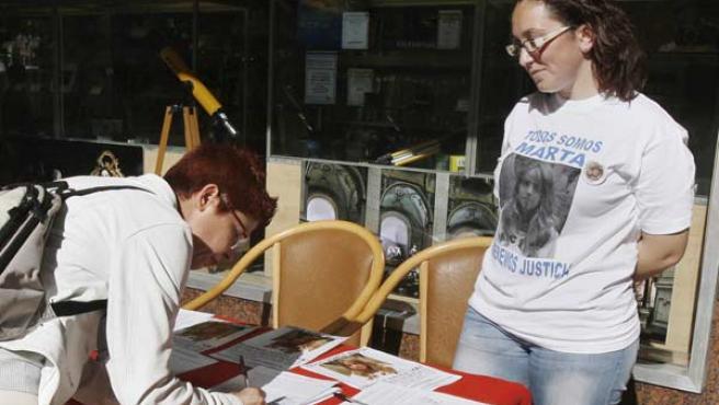 Una mujer firma para lograr un referendo por la cadena perpetua, en la campaña organizada por los padres de Marta del Castillo.