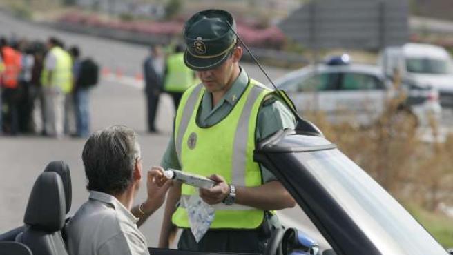 Un agente de la Guardia Civil realiza un test de alcholemia a un conductor.