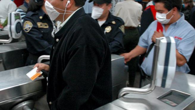 Viajeros mexicanos en el metro con mascarillas debido al brote de gripe porcina.