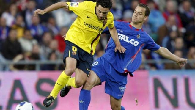 El centrocampista del FC Barcelona Xavi Hernández (i) regatea al delantero del Getafe CF Roberto Soldado.