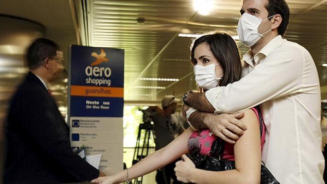 Una pareja protegida con mascarillas espera la llegada de familiares procedentes de México en el aeropuerto de Sao Paulo.