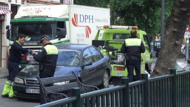 La grúa se lleva un vehículo que acaba de multar la Policía Local.