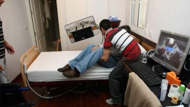 Unos familiares cuidan a un hombre dependiente.