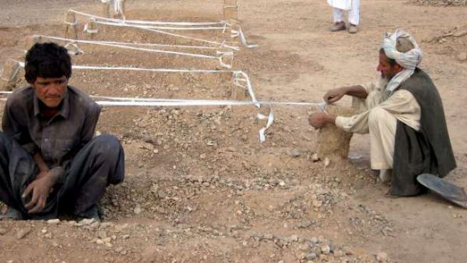 Un grupo de hombres junto a unas tumbas tras un bombardeo estadounidense en la provincia afgana de Farah.