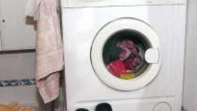 Una mujer muestra su lavadora.