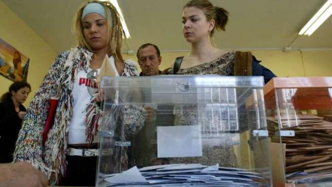 Dos jóvenes, ante una urna en elecciones pasadas en Zaragoza.