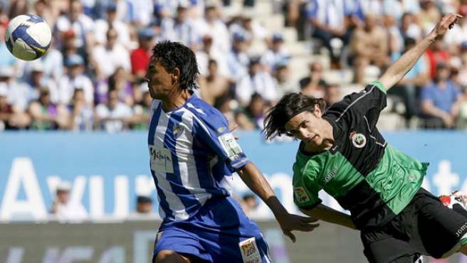 El defensa brasileño del Málaga CF Weligton Pena despeja un balón ante el centrocampista del Racing de Santander Toni Moral.