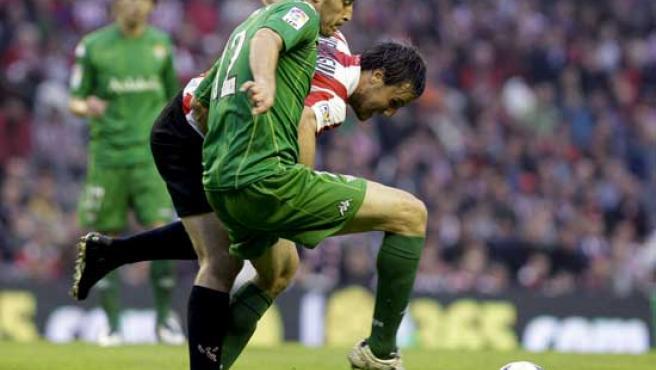 El centrocampista del Athletic Carlos Gurpegui (atrás) lucha por el balón con el defensa del Betis Damiá Abella.