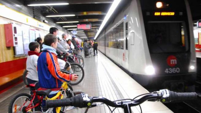 Varios ciclistas contemplan el paso de un convoy sin servicio en una estación del metro de Valencia.